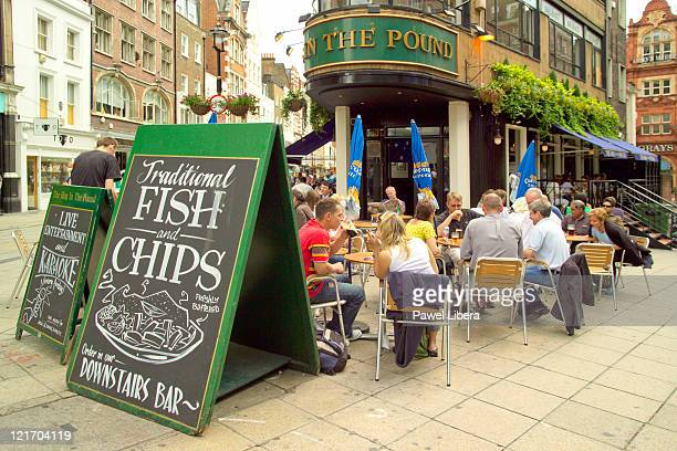People Eating at Fish and Chips Shop in Oxford Street, West End, London, UK