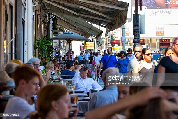 People eating at outdoor tables in downtown Rome, Italy