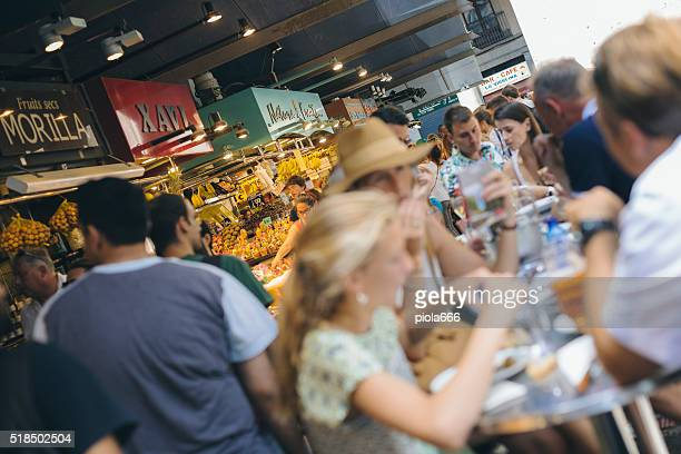 people eating at the boqueria market in barcelona - tapas stock photos and pictures