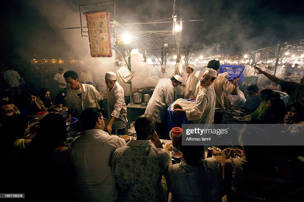 CONTENT] People Eating Dinner at the food stalls in Jamaa el Fna square, Marrakesh, Morocco (north Africa).