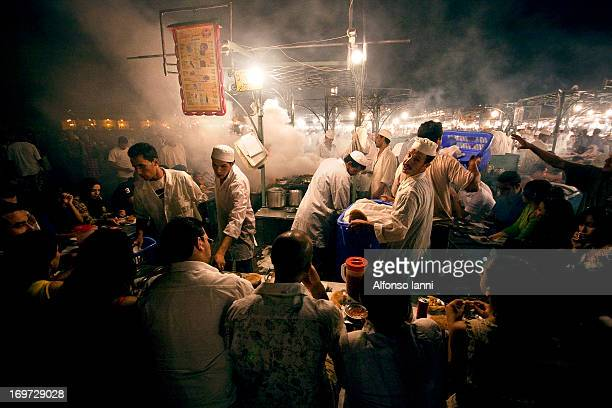 People Eating Dinner at the food stalls in Jamaa el Fna square, Marrakesh, Morocco .