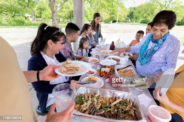 家族の再会の間に食べる人々 - ポットラック ストックフォトと画像