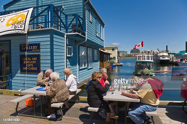 people eating fish and chips, fishermans wharf, victoria, vancouver island, british columbia, canada - vancouver island stockfoto's en -beelden