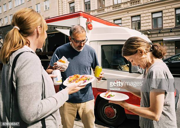 People eating food while standing by truck at city street