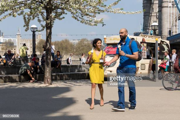 People eating ice cream in the sunshine on the South Bank next to Tower Bridge during hot and sunny weather on April 20 2018 in London England...