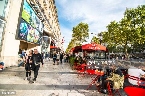 people eating in a cafe on avenue des champs-elysees, paris - brasserie stock pictures, royalty-free photos & images