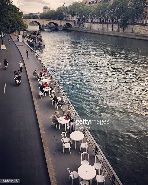 People eating in Paris cafe on Seine riverbank, France
