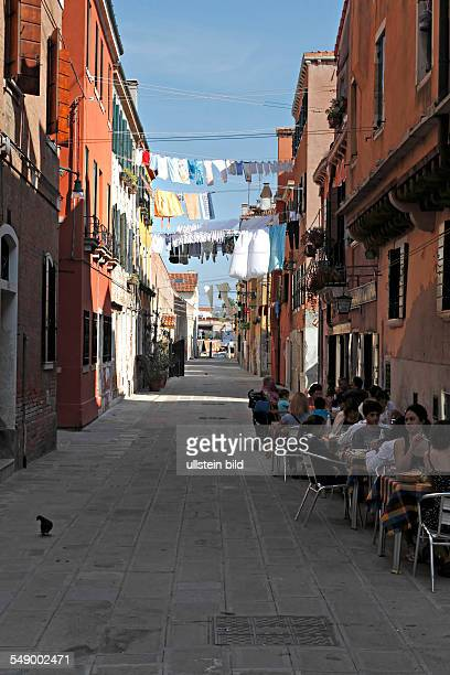 People eating outside a little Restaurant in a small street full of clothes lines Sestiere Castello Venice Italy