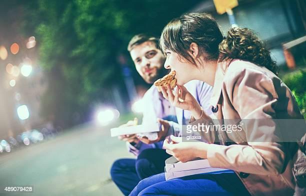 Personas de comer pizza en la calle.