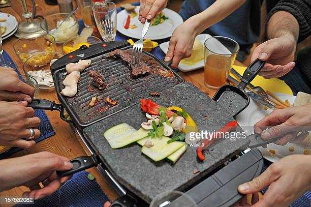 people eating raclette - grill and hands