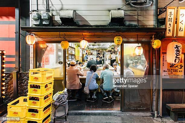People eating ramen in local restaurant in Yakitori alley, Shinjuku, Tokyo, Japan