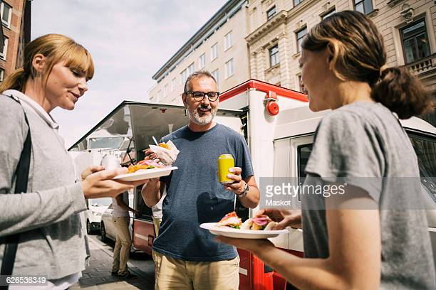 People eating snacks while standing against truck at city