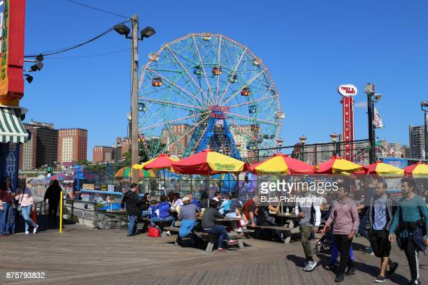 People eating under umbrellas at Nathan's Famous Hot Dogs & Restaurant along the boardwalk at Coney Island, Brooklyn, New York City