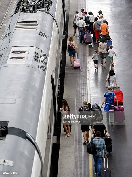 People embark onto a train at Madrid's Atocha station on August 21 2015 AFP PHOTO / DANI POZO