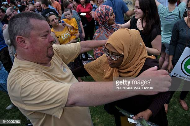 People embrace after being encouraged to hug during a vigil outside the Dr Phillips Center for the Performing Arts for the mass shooting victims at...