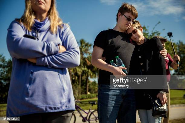 People embrace as students participate during the ENOUGH National School Walkout rally at Marjory Stoneman Douglas High School in Parkland Florida US...
