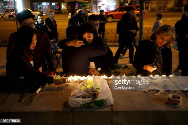 People embrace as they lay candles and leave messages at a memorial for victims of a crash on Yonge St at Finch Ave after a van plowed into...