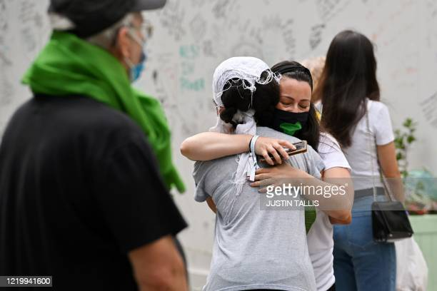 People embrace as they pay their respects beside a wall where messages of support have been written surrounding Grenfell tower in west London on June...