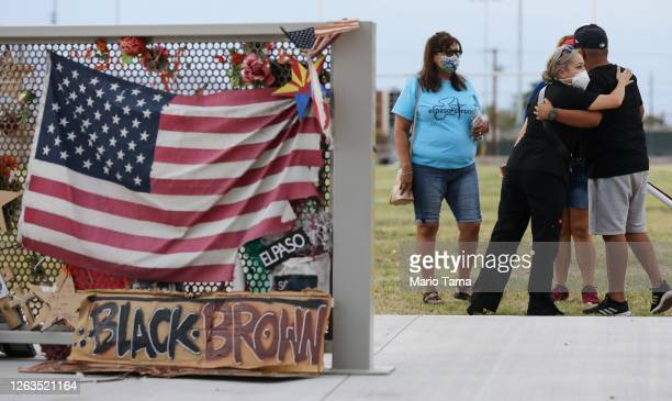 People embrace at a temporary memorial in Ponder Park honoring victims of the Walmart shooting which left 23 people dead in a racist attack targeting...