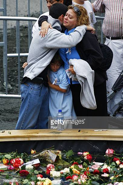 People embrace at the edge of a reflecting pool filled with flowers during a ceremony commemorating the 911 terrorist attacks at the World Trade...