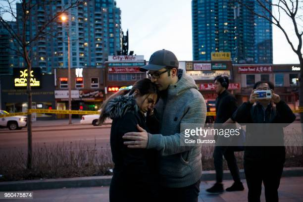 People embrace at the scene of a memorial for victims of a crash at Yonge St at Finch Ave after a van plowed into pedestrians on April 23 2018 in...
