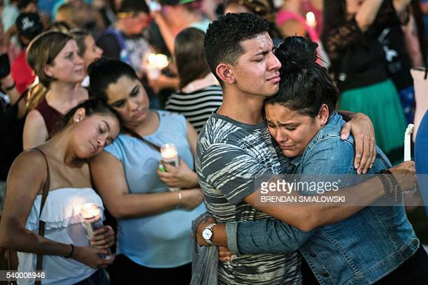 People embrace during a vigil outside the Dr Phillips Center for the Performing Arts for the mass shooting victims at the Pulse nightclub June 13...