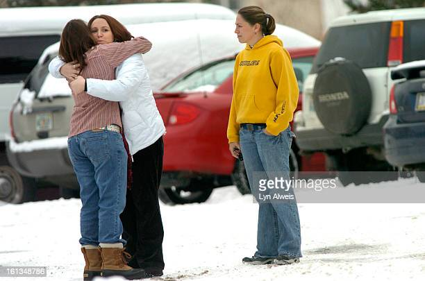 People embrace on a snowy Tuesday, Dec. 11, in the parking lot of Youth With A Mission, or YWAM, in Arvada, Colorado. Early Sunday morning a man with...