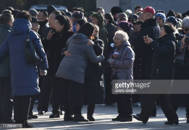 People embrace outside the funeral of Li Rui the former secretary to late communist leader Mao Zedong at the Babaoshan cemetery in Beijing on...