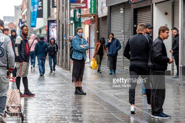 People employ social distancing as they queue at shops in Dublin City centre in Ireland on May 18 as Ireland cautiously begins to lift it's...
