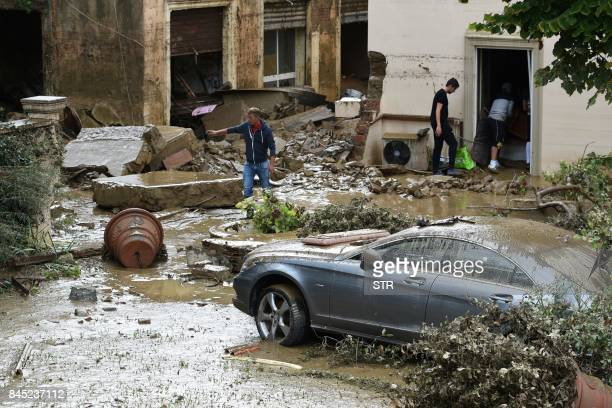 TOPSHOT People empty a house in the Livorno area flooded after heavy rain on September 10 2017 At least six people have died in violent rainstorms...