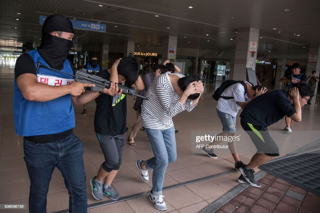 People enact a mock hostage situation during an anti-terror drill in Goyang on August 21, 2017. Meanwhile tens of thousands of South Korean and US troops are taking part in the 'Ulchi Freedom Guardian' joint military drills, a largely computer-simulated exercise that runs for two weeks in the South. / AFP PHOTO / Ed JONES