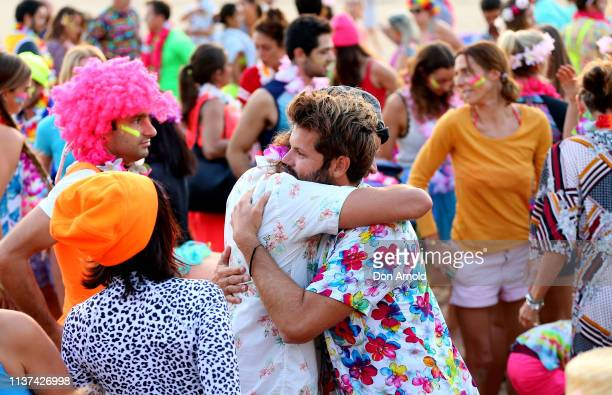 People engage in a symbolic hug on Bondi Beach on March 22 2019 in Sydney Australia Surfers gather to celebrate five years of OneWave a not for...
