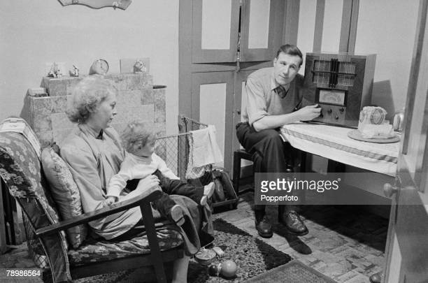 People, England A family couple sitting in the lounge with their young child listen to the radio