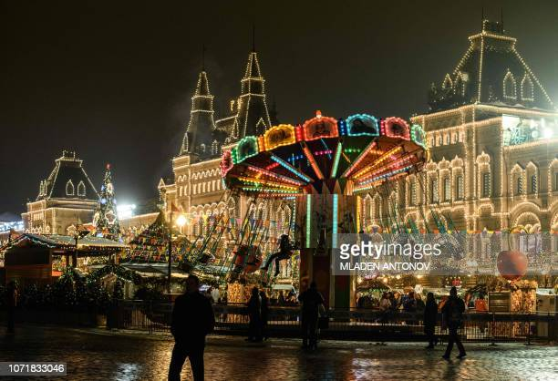 People enjoy a chair swing ride during the Christmas and New Year market in front of the GUM department store decorated with festive lights on the...