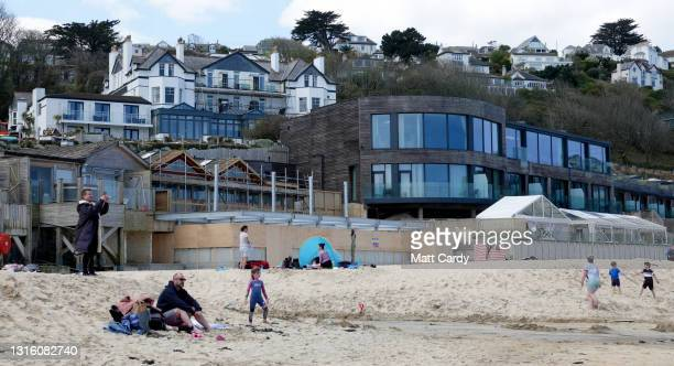 People enjoy a day on the beach in front of The Carbis Bay Hotel and Estate at Carbis Bay, which is set to be the main venue for the upcoming G7...