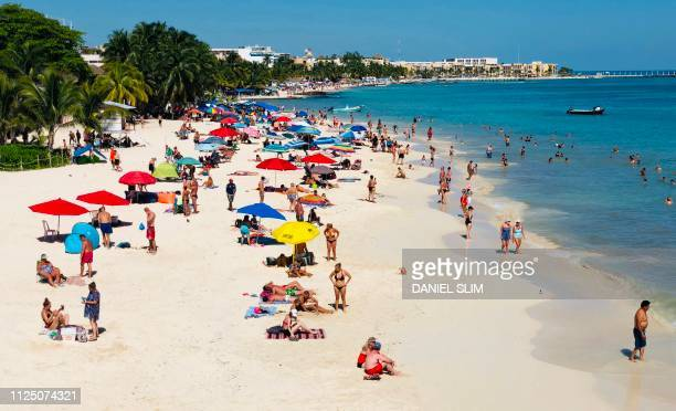 People enjoy a day on the beach in the seaside tourist resort of Playa del Carmen Quintana Roo State on February 15 2019 Playa del Carmen and nearby...