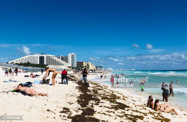 People enjoy a day on the beach in the seaside tourist resort of Cancun in Quintana Roo state Mexico on February 16 2019 Playa del Carmen and Cancun...