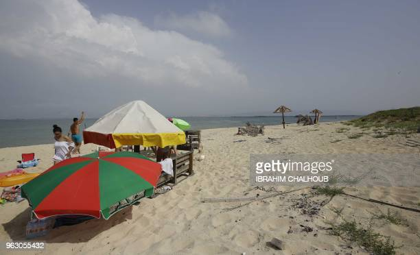 People enjoy a day on the Palm Island natural reserve near the coast of the Mina district of Tripoli in northern Lebanon on May 27 2018