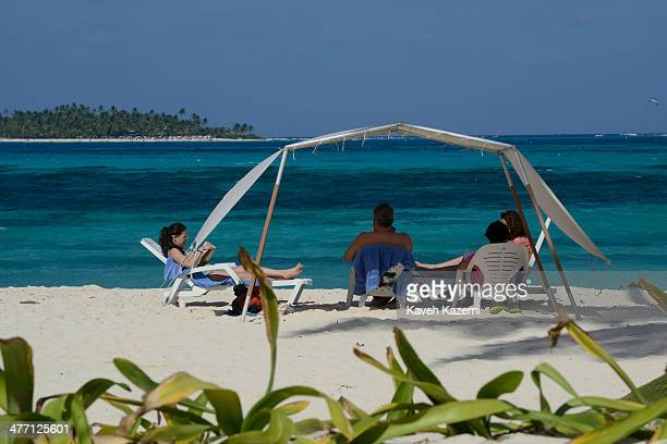 People enjoy a day on the sandy beach under the shade with the sea in the background on January 24 2014 in San Andres Colombia Colombia has a...