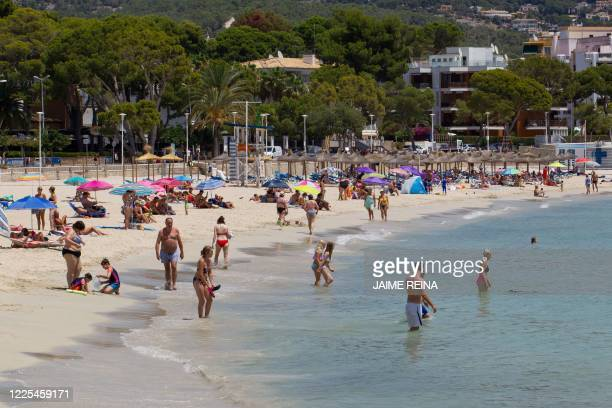People enjoy a day out at Es Carregador Beach in Calvia on the Spanish island of Mallorca on July 8 2020 The Balearic Islands are expecting a wave of...