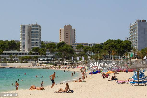 People enjoy a day out at Magaluf Beach in Calvia on the Spanish island of Mallorca on July 8, 2020. - The Balearic Islands are expecting a wave of...