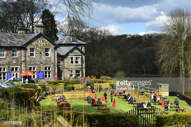 People enjoy a drink and food whilst in a beer garden at Hotel Rudyard on April 12, 2021 in Leek, England. England has taken a significant step in...