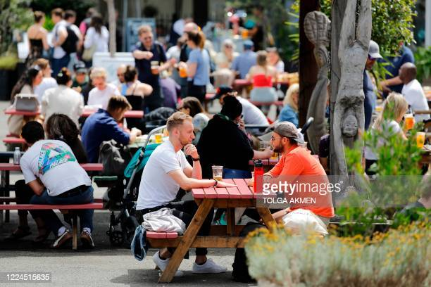 People enjoy a drink at Gabriel's Wharf beside the River Thames in London on July 3 2020 The government has been easing stayathome orders imposed in...