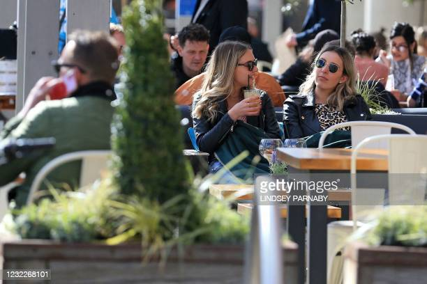 People enjoy a drink at tables outside The Lock Kitchen and Bar in the afternoon sunshine in Leeds, northern England on April 12 as coronavirus...