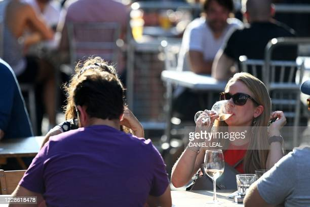 People enjoy a drink in the late summer sunshine at outside tables in Soho central London on September 20 2020 as the British government consider...