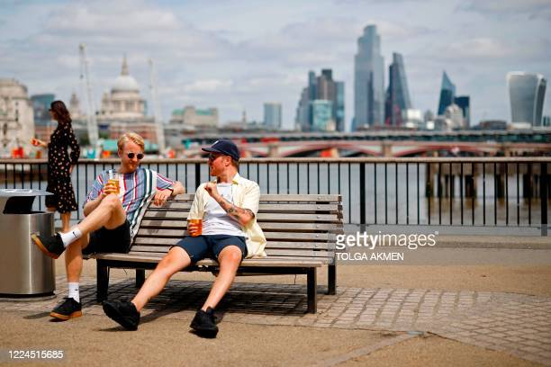 People enjoy a drink in the sunshine beside the River Thames in London on July 3 2020 The government has been easing stayathome orders imposed in...