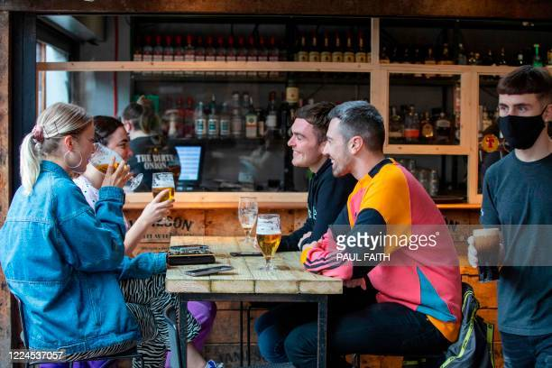 People enjoy a drink inside the Dirty Onion in Belfast on July 3 as pubs open their doors after the enforced closure due to the coronavirus pandemic....