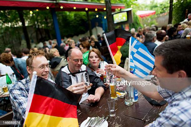 People enjoy a drink next to German and Greek national flags as they watch the EURO 2012 quarter-final football match between Germany and Greece on...