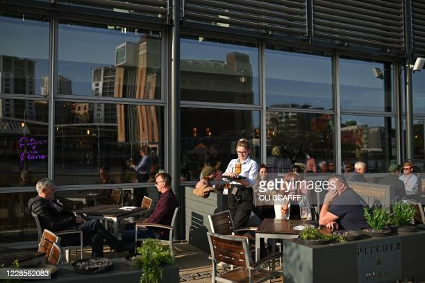 People enjoy a drink on the quayside in the early evening sunshine on the banks of the River Tyne in Newcastle upon Tyne northeast England on...