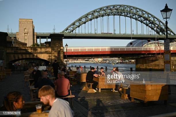 People enjoy a drink on the quayside in the early evening sunshine, on the banks of the River Tyne in Newcastle upon Tyne, north-east England, on...